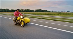 Leon Logothetis riding his yellow motorbike, Kindness One, on his journey where he performs random acts of kindness to strangers.