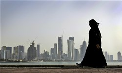In this May 14, 2010 file photo, a Qatari woman walks in front of the city skyline in Doha, Qatar. An investigation into why a British man fell to his death on a Qatar World Cup site has raised concerns about stadium roof safety. Acting as a mediator, Kuwait has presented Qatar a long-awaited list of demands from Saudi Arabia, Bahrain, the United Arab Emirates and Egypt, four Arab nations that cut ties with Qatar in early June 2017.