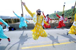 Ian Asenjo, center, and other members of CMU Bhangra, a group comprising Carnegie Mellon University students, perform on the West End Bridge during OpenStreetsPGH in June. Bhangra is a folk dance that originated in Punjab, northern India.