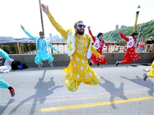 Ian Asenjo, center, and other members of CMU Bhangra, a group composed of Carnegie Mellon University students, perform on the West End Bridge during Sunday's Open Streets PGH event. Bhangra is a folk dance that originated in Punjab, northern India.