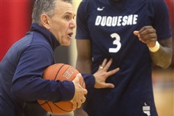 Head coach Keith Dambrot demonstrates how to protect the ball during a Duquesne University men's basketball practice on Tuesday, June 20, 2017 at the A.J. Palumbo Center in Uptown.