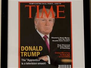 A framed portrait of President Donald Trump on the cover of a Time Magazine and other magazine covers framed and hanging from a wall at the Trump National Doral Miami Golf Shop.