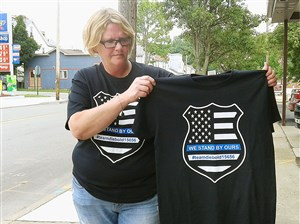 Tracy Schaeffer of the Leechburg-based T-shirt company Little Devil's Imprints holds a shirt she is selling to raise funds for police Chief Michael Diebold's medical expenses after he was injured in a fireworks accident Saturday night.