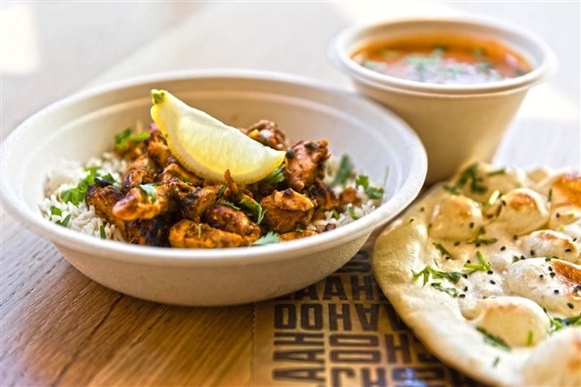 Chicken barbecue is cooked in a 600-degree tandoor oven and served with a side of tikka masala along with naan.