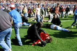In this April 15, 1989 file photo, police, stewards and supporters tend and care for wounded supporters on the pitch at Hillsborough Stadium, in Sheffield, England.