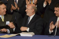 Democratic Gov. Tom Wolf shakes hands with Senate Majority Leader Jake Corman earlier this month after signing legislation. At right is House Majority Leader Dave Reed.