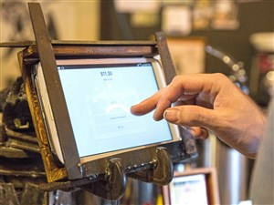 Chase McBryde uses a tablet to pay for his coffee at the Black Forge Coffee House Wednesday in Allegntown. Mr. McBryde designed the sign for the coffee house and other new businesses in the neighborhood to help grow the community.