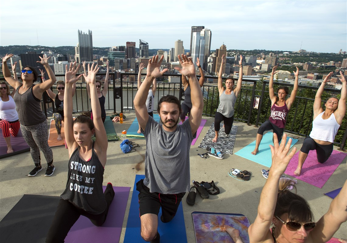 Renee Massa of Green Tree and T.J. Heromin of Mount Washington enjoy yoga at sunset with MoWa Yoga on the Monongahela Incline's overlook, instructed by yogi Amanda Rubio, left, in sunglasses.
