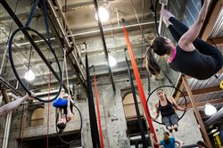 Jenly Deiter, left, co-owner of Iron City Circus Arts, demonstrates a move on an aerial hoop for Djuna Gulliver of Lawrenceville, center, and Justine Vanella of Brookline, right, during a class.