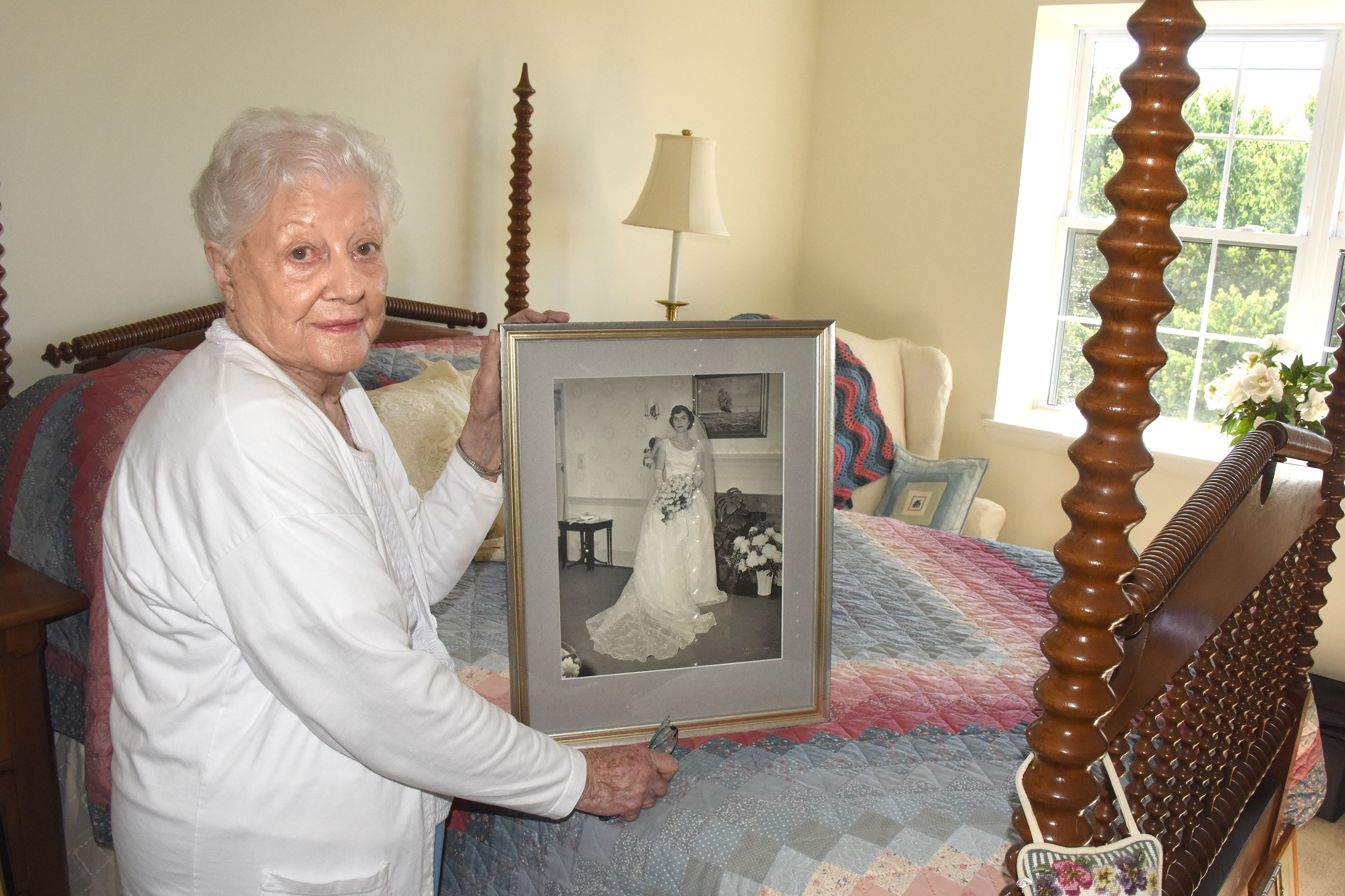 20170609dsDownsizingHomesPremiumMag08-6  Betty Price, formerly of Fox Chapel, holds a portrait of herself in on her wedding day one of several photos she kept for her move into Longwood at Oakmont Retirement Home.