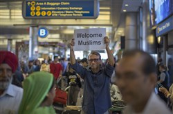 "John Wider carries a welcome sign near arriving Sikh travelers at Los Angeles International Airport on the first day of the the partial reinstatement of the Trump travel ban Thursday. Under a Supreme Court order, foreigners who do not have a so-called ""bona fide relationship"" with a person or entity in the United States can be banned. The ban effects travelers from Iran, Libya, Somalia, Sudan, Syria and Yemen."