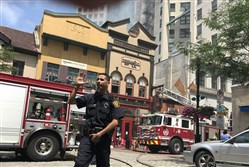 Police move back onlookers as firefighters respond to a fire at Nicholas Coffee in Market Square, Downtown on June 30, 2017. Damage caused by the blaze is now the subject of a federal lawsuit.