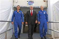 Vice President Mike Pence, center, is flanked by NASA astronaut Reid Wiseman, left, and Patrick Forrester, NASA chief astronaut, as they walk out of crew headquarters at the Kennedy Space Center in Cape Canaveral, Fla., on July 6.