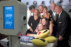 Clockwise:  Vince Pascoe, Gina Pascoe, Dan DelBianco, Michelle DelBianco, Reid Smith, Ed Haney, Amy Weinstock and Sue Haney pose in front of a photo booth during Pittsburgh Vintage Grand Prix's Black Tie & Tailpipes event.