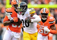 Le'Veon Bell fights off Browns defenders last November in Cleveland.