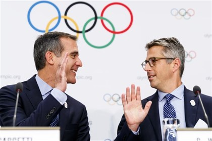 Eric Garcetti, mayor of Los Angeles, left, and Casey Wasserman, chairman of Los Angeles 2024, high-five during a press conference after a presentation at a International Olympic Committee (IOC) members meeting in Switzerland Tuesday.