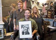 Aaron Stubna, front, holds a photo of his grandfather, the original owner of Lincoln Barber Shop in Bellevue. Behind him is his son, Rourke Stubna, and his aunt, Roe Rizor, who also work in the shop, which has employed four generations of barbers.