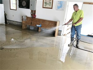 Bill Stewart of McDonald uses a hose July 12 to clean mud from the floor of his garage after he said floodwaters from the Southern Beltway construction across Route 980 washed out his property.