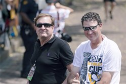 Penguins co-owners Ron Burkle and Mario Lemieux ride through the crowd during the Penguins victory parade in June 2017.