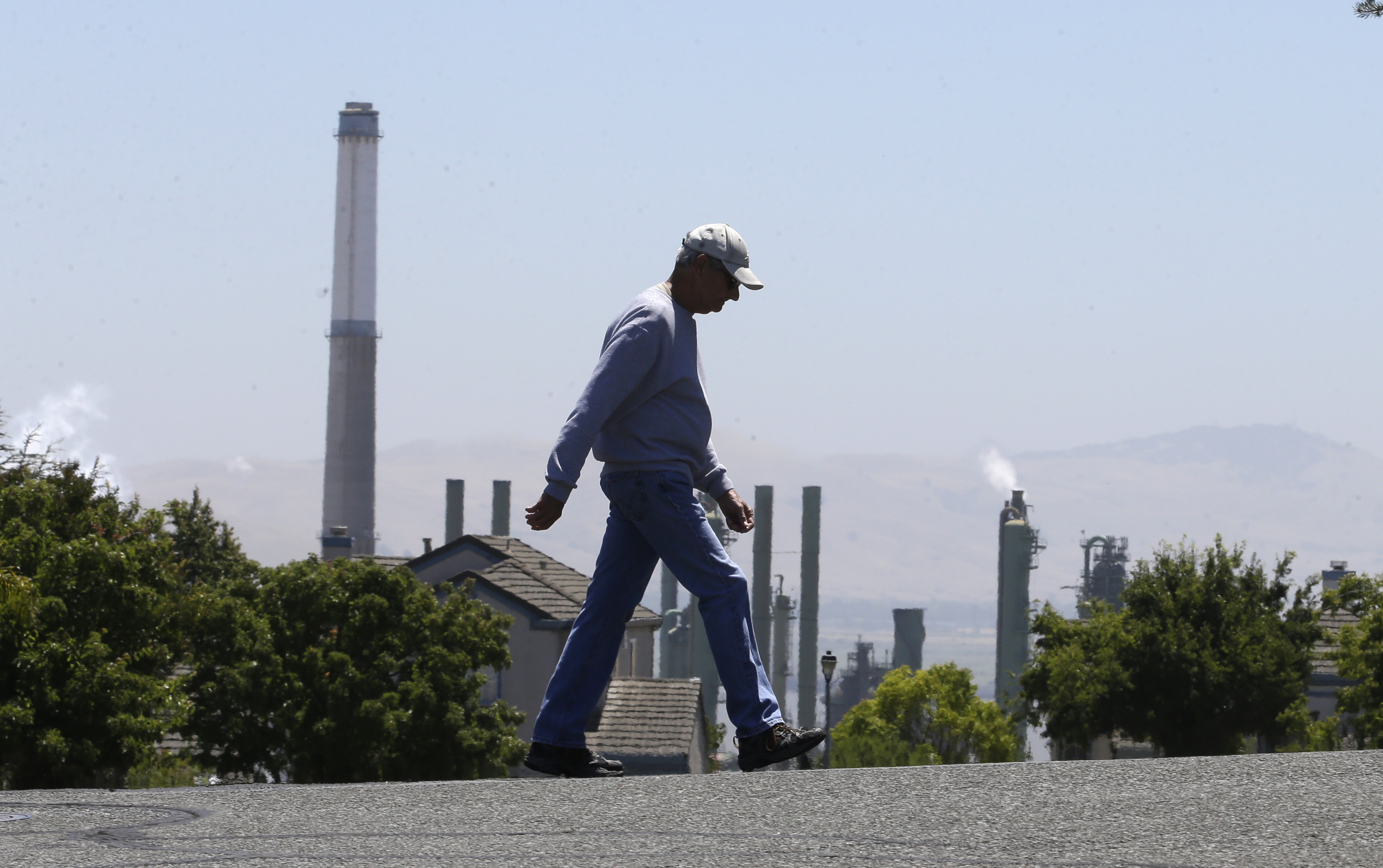 California Climate Change Q and A-1 The stacks from the Valero Benicia Refinery are seen as a pedestrian walks in a nearby neighborhood, Wednesday, July 12, 2017, in Benicia, Calif. California Gov. Jerry Brown is racing to convince state lawmakers to extend California's cap-and-trade program which puts a price on carbon emitted by polluters, including oil refineries. The program has been closely watched around the world as a market-based way to reduce greenhouse gas emissions, but it expires in 2020. (AP Photo/Rich Pedroncelli)