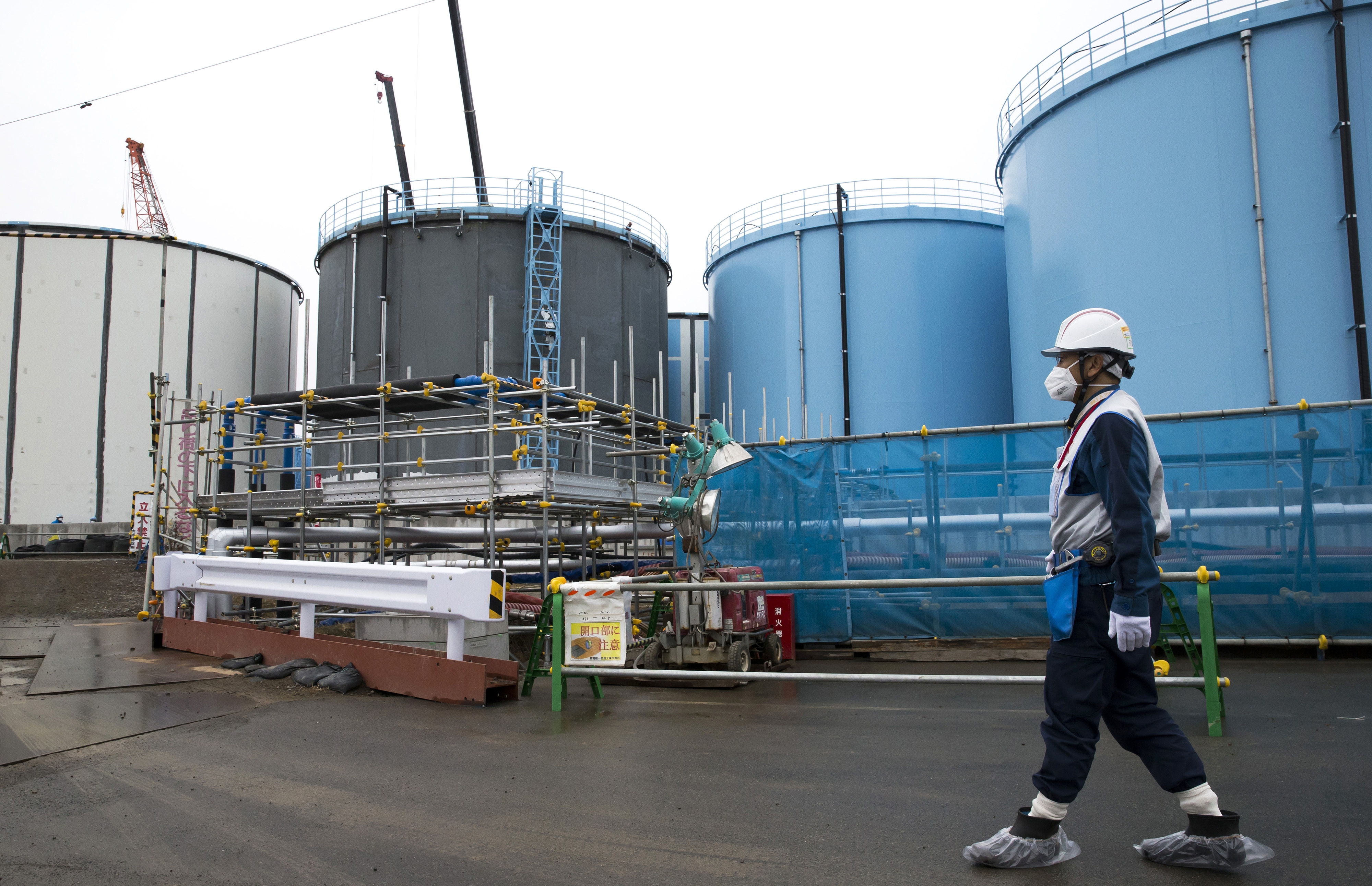Japan Nuclear-2 FILE - In this Feb. 23, 2017, file photo, an employee walks past storage tanks for contaminated water at the tsunami-crippled Fukushima Dai-ichi nuclear power plant of the Tokyo Electric Power Co. (TEPCO) in Okuma town, Fukushima prefecture, Japan. Massive amounts of radiation-contaminated water that has been processed and stored in hundreds of tanks at the plant are hindering decommissioning work and pose a safety risk in case another massive quake or tsunami strikes. TEPCO needs to release the water - which contains radioactive tritium that is not removable but considered not harmful in small amounts - into the Pacific Ocean, TEPCO's new Chairman Takashi Kawamura said. (Tomohiro Ohsumi/Pool Photo via AP, File)