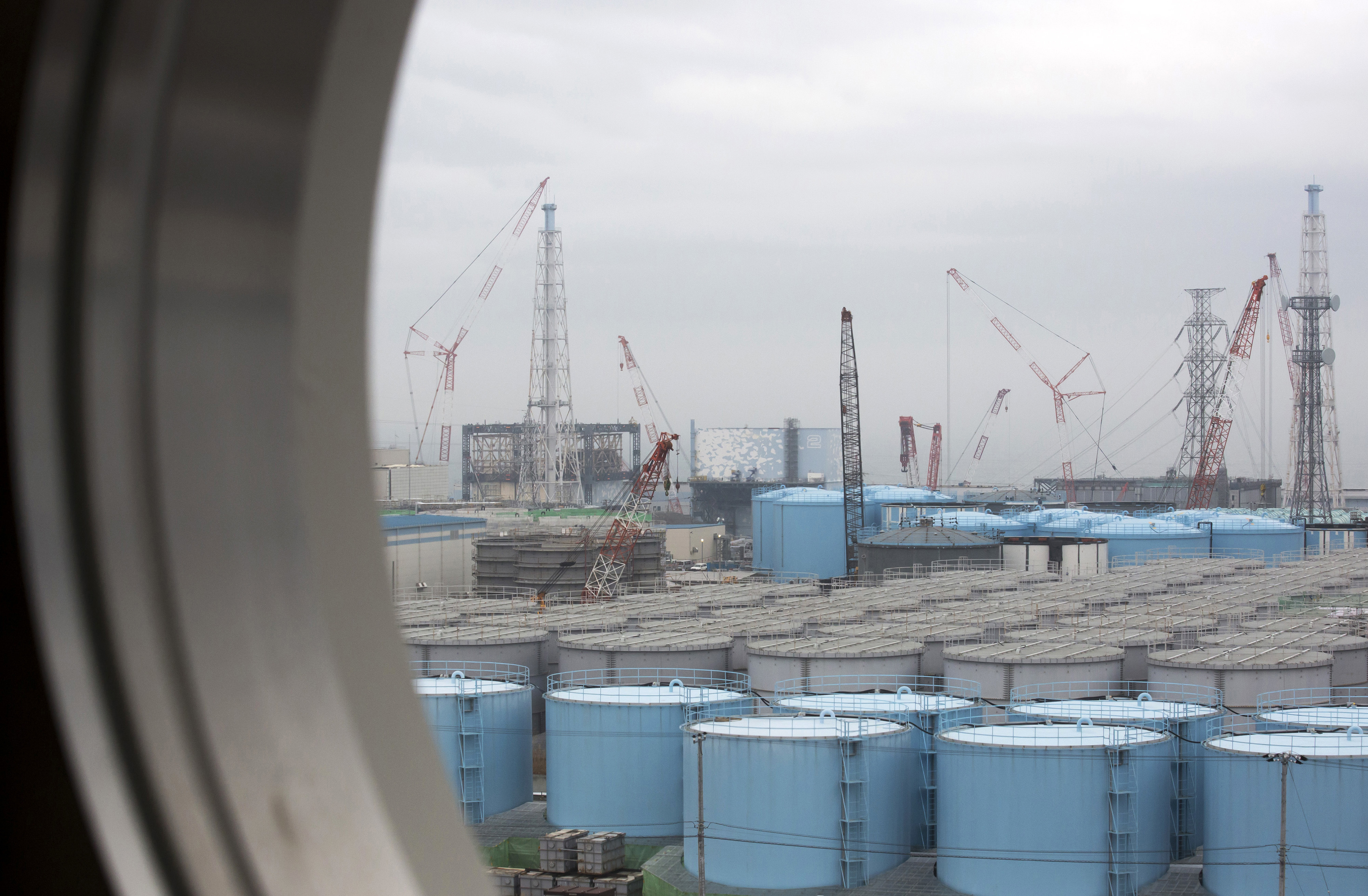 Japan Nuclear-3 FILE - In this Feb. 23, 2017, file photo, storage tanks for contaminated water are seen through a window of a building during a media tour to the tsunami-crippled Fukushima Dai-ichi nuclear power plant of the Tokyo Electric Power Co. (TEPCO) in Okuma town, Fukushima prefecture, Japan. Massive amounts of radiation-contaminated water that has been processed and stored in hundreds of tanks at the plant are hindering decommissioning work and pose a safety risk in case another massive quake or tsunami strikes. TEPCO needs to release the water - which contains radioactive tritium that is not removable but considered not harmful in small amounts - into the Pacific Ocean, TEPCO's new Chairman Takashi Kawamura said. (Tomohiro Ohsumi/Pool Photo via AP, File)