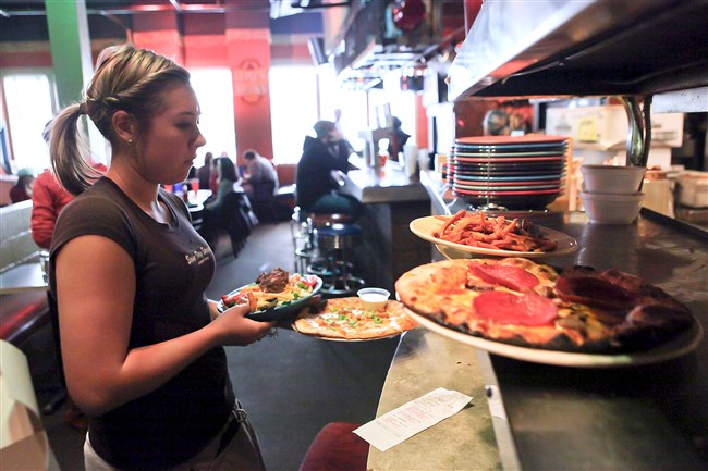 An employee at Fuel & Fuddle does a balancing act while serving up piping hot pizza and fries.