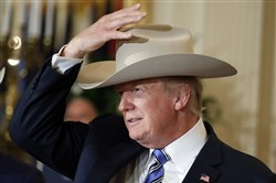"President Donald Trump tries on a Stetson hat during a ""Made in America"" product showcase featuring items created in each of the 50 U.S. states on Monday at the White House in Washington."
