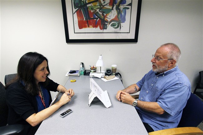 In this July 6 photo, Kim Mueller, left, administers a test to Alan Sweet, in which he describes an illustration, as part of a University of Wisconsin-Madison study on dementia.