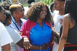A woman identified as the mother of Terrell Wright, one of the two victims in Tuesday double-fatal shooting in Larimer, is comforted Tuesday by friends and family.