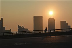 A runner gets an early workout in along Grandview Avenue on Mount Washington as a hazy sun hangs over the Pittsburgh skyline Wednesday.