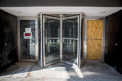 A door at the entrance of the abandoned Macy's building is boarded up with plywood on Tuesday, July 18, 2017, in Downtown.
