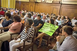 Eva Resnick-Day of Friendship holds a sign during a public hearing on affordable housing in the City Council Chambers, Downtown, on Tuesday.