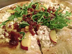 The grilled peach pizza with feta cheese, arugula and crispy proscuitto at Eighth & Hays in Homestead.