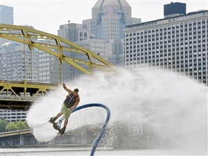 "Gavin Melan , of Belle Vernon , Pa makes a wide turn while ""fly boarding"" against a backdrop of the Pittsburgh skyline as part of the Jet Ski Stunt Shows to promote the upcoming August 4-6 EQT Pittsburgh Three Rivers Regatta, Wednesday, July 19, 2017. (Darrell Sapp/Pittsburgh Post-Gazette via AP)"