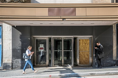 People walk past the entrance to the former Macy's/Kaufmann's building Downtown on Tuesday.