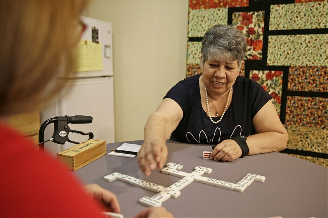 A special PET scan enabled precise diagnosis of the dementia afflicting Cynthia Guzman, shown here still able to play dominoes.