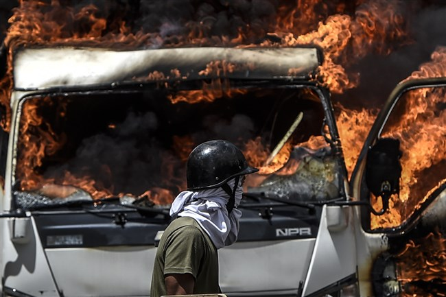 A truck set ablaze by opposition activists blocking an avenue during a protest burns in Caracas on Tuesday.