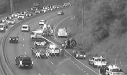 A vehicle that rolled over, at right, on the Parkway West early Thursday morning had traffic backed up in the outbound and inbound lanes.