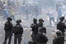 Palestinians run from tear gas on Friday in Jerusalem.