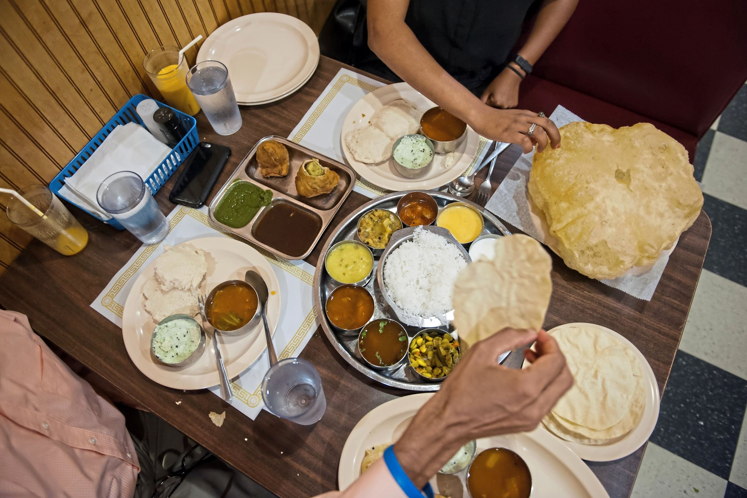 20170719smsEatWithHands03-2 Ganesh Viswanathan and Fitale Wari use their hands to eat the pappadum and bhatura at Udipi Cafe in Monroeville.