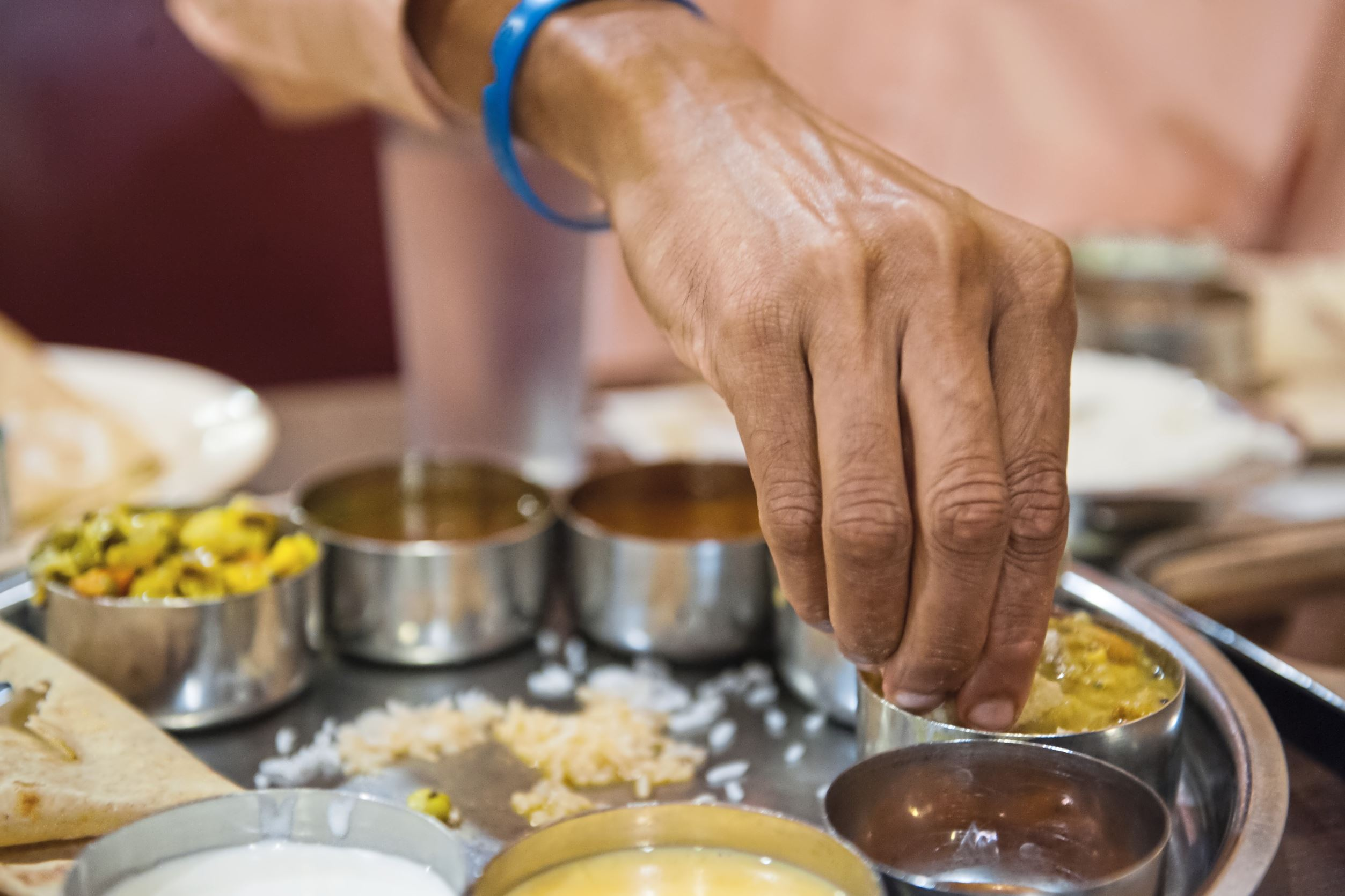 20170719smsEatWithHands02-1 Ganesh Viswanathan of Upper St. Clair uses his fingers to eat a South Indian thali at Udipi Cafe in Monroeville.