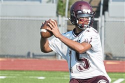 Uniontown quarterback Omar Teets looks for an open receiver during a scrimmage against California at Uniontown High School on July 19, 2017.