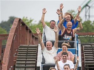 Rollercoaster riders wave their arms Saturday as they go down a hill during a celebration for the Racer's 90th birthday on at Kennywood.