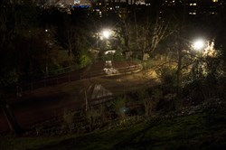 Gardens in gloomy night-time lighting at Buttes-Chaumont, a public park in northeastern Paris.