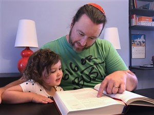 "Chris Hall, the head of adult education at Beth Shalom, studies with his daughter Ada. Since he converted to Judaism at a conservative synagogue as an adult, his religious practice is central to his life. ""I was shocked and dismayed that somehow this very abstract issue would be suddenly made so personal and so direct as to be directed to the Rabbi of my synagogue,"" he said."