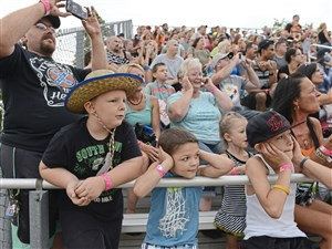 From left Willard Friend, Jr., with his son Willard Friend III, of Brownsville, and Jeremiah Daugherty, 7, Brooklyn Sanders, 5, T.J. Daugherty, 11, and Mary Daugherty, all of Brownsville, watch as two Monster Trucks rev their engines before racing across the Chevron Arena at the Fayette County Fair in Dunbar, Pa. in August of 2016.