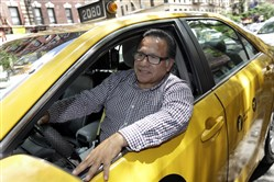 In this June 26 photo, taxi driver and taxi medallion owner Marcelino Hervias poses for photos with his taxicab on New York's Upper West Side. People who dole out cash to save time on things like housekeeping, delivery services and taxis are a little bit happier than those who don't, new research finds.