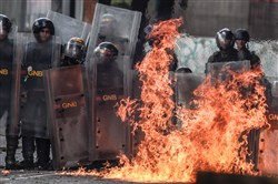 A Molotov cocktail thrown by anti-government activists explodes near members of the National Guard during clashes in Caracas, Venezuela, on Wednesday during a 48-hour general strike called by the opposition.