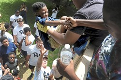 Pitt quarterback Kenny Pickett, bottom with hand raised, and his teammates, help Jeremy Franklin, 8, of Highland Park climb the obstacle wall drill at the Mel Blount Youth Leadership Initiative Wednesday in Claysville, Pa.